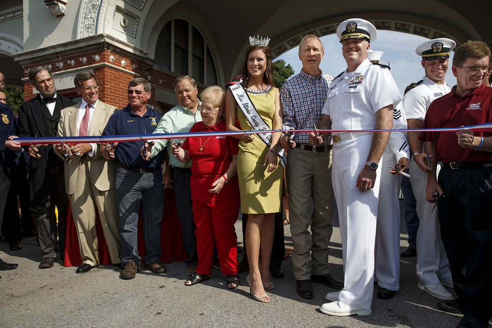 Illinois Gov. Bruce Rauner was flanked by Miss Illinois County Fair Queen Sadie Gassmann and Jessie Porter, Commanding Officer for the USS Illinois (SSN-786), a Virginia Class nuclear submarine, and other dignitaries as he cut the ribbon to officially open the 2015 Illinois State Fair Friday, Aug. 14, 2015.  Ted Schurter/The State Journal-Register