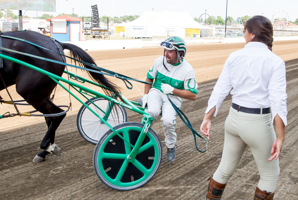 Driver Pat Curtin hops on the sulky of Bc's Belle Street after leaving the winner circle for his fourth win of the day during harness racing at the Illinois State Fairgrounds, Friday, Aug. 14, 2015, in Springfield, Ill. Justin L. Fowler/The State Journal-Register