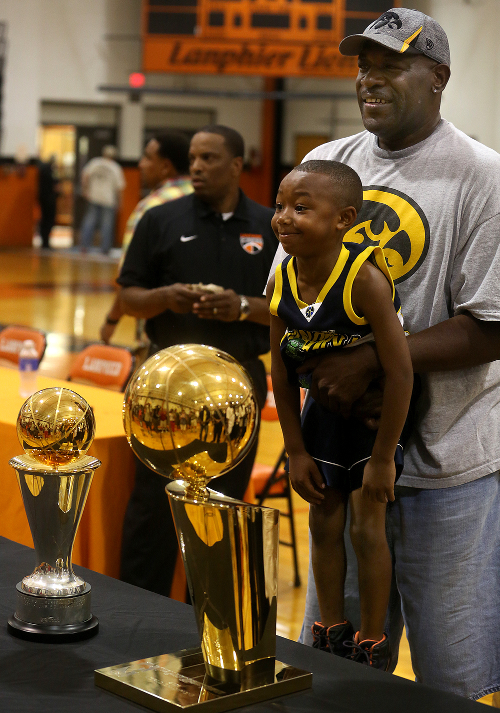 Former NBA player Ed Horton of Springfield, who played for Lanphier High School, picks up his son Ed Horton Jr., 6, while getting their photo taken with the NBA championship and NBA Finals MVP trophies before the start of the ceremony. David Spencer/The State Journal-Register