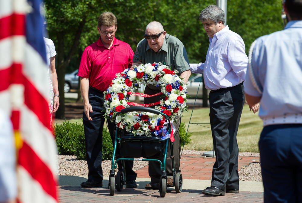 "WWII Marine Corps veteran Jesse Beanblossom, center, lays a wreath with the help of Springfield Mayor Jim Langfelder, left, and his son Todd Beanblossom, right, during a ceremony to commemorate the 70th anniversary of the end of WWII at Camp Butler National Cemetery, Sunday, Aug. 16, 2015, in Springfield, Ill. The event was part of ceremonies across the country for the ""Spirit of 45"" initiative and as a way to say thanks to veterans of the Greatest Generation. Mayor Langfelder was there to represent his father, Ossie Langfelder, a WWII veteran, who was unable to attend due to the heat. Justin L. Fowler/The State Journal-Register"