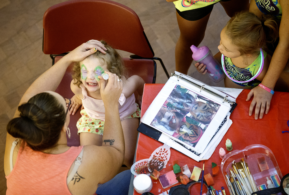 Caroline Bryans squints her eye as Genna Best applies glitter to her face paint during a back-to-school party at the Abraham Lincoln Presidential Library Monday, Aug. 10, 2015. The library and museum collected more than 700 school backpacks from visitors for needy students in Springfield. Ted Schurter/The State Journal-Register