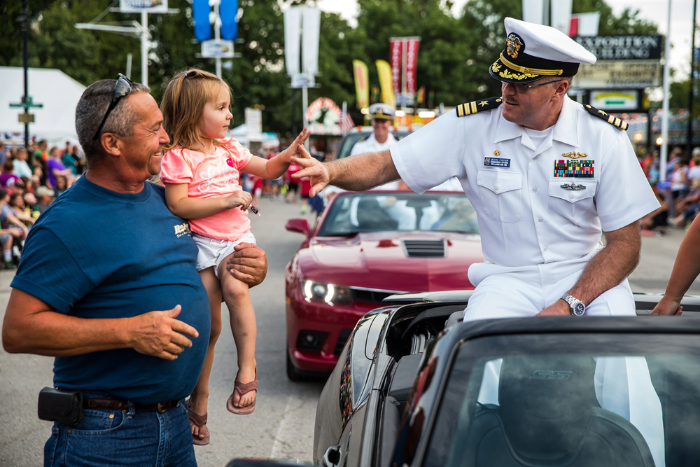 Molly Willis, 2, gets a lift from her grandfather, David Willis, to get a high five from Navy Cmdr. Jessie Porter, the 2015 Illinois State Fair Grand Marshal, during the Illinois State Fair Twilight Parade at the Illinois State Fairgrounds, Thursday, Aug. 13, 2015, in Springfield, Ill. Justin L. Fowler/The State Journal-Register