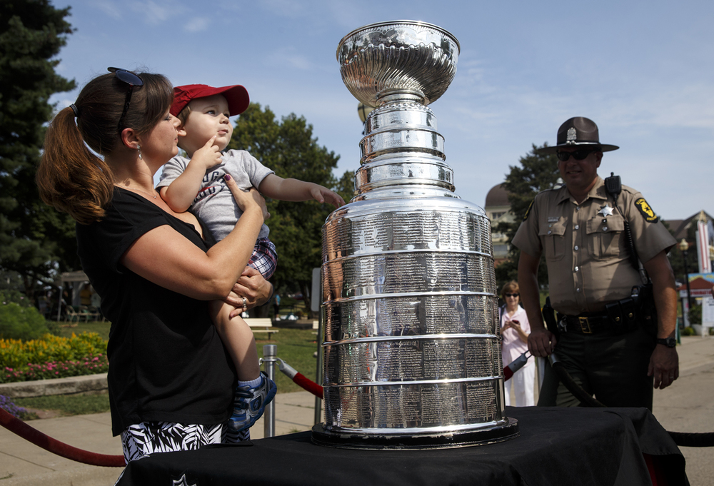 Robyn McCracken of Springfield holds her two-year-old son Robert as he inspects the Stanley Cup on display near the main gate of the Illinois State Fairgrounds Friday, Aug. 14, 2015. The Chicago Blackhawks have won the Cup in two of the last three seasons.  Ted Schurter/The State Journal-Register