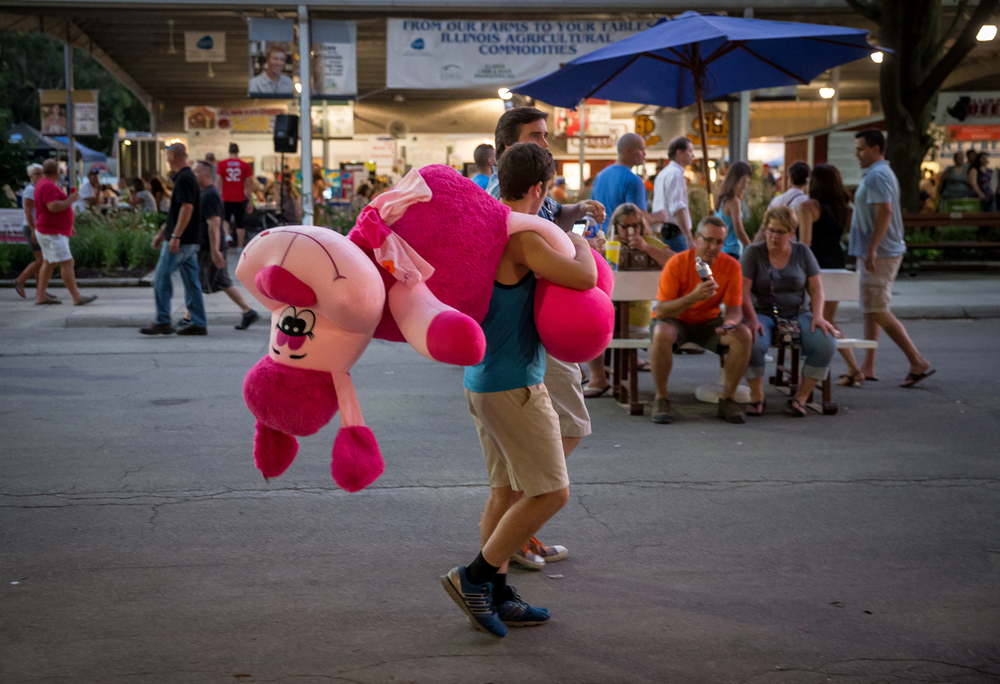 Kaleb Hefford, of Morris, Ill., carries a stuffed animal in front of the Grandstand that he won in a ring toss game at the Illinois State Fairgrounds, Saturday, Aug. 15, 2015, in Springfield, Ill. Hefford planned to take the stuffed animal back home to his girlfriend that just had her wisdom teeth removed. Justin L. Fowler/The State Journal-Register