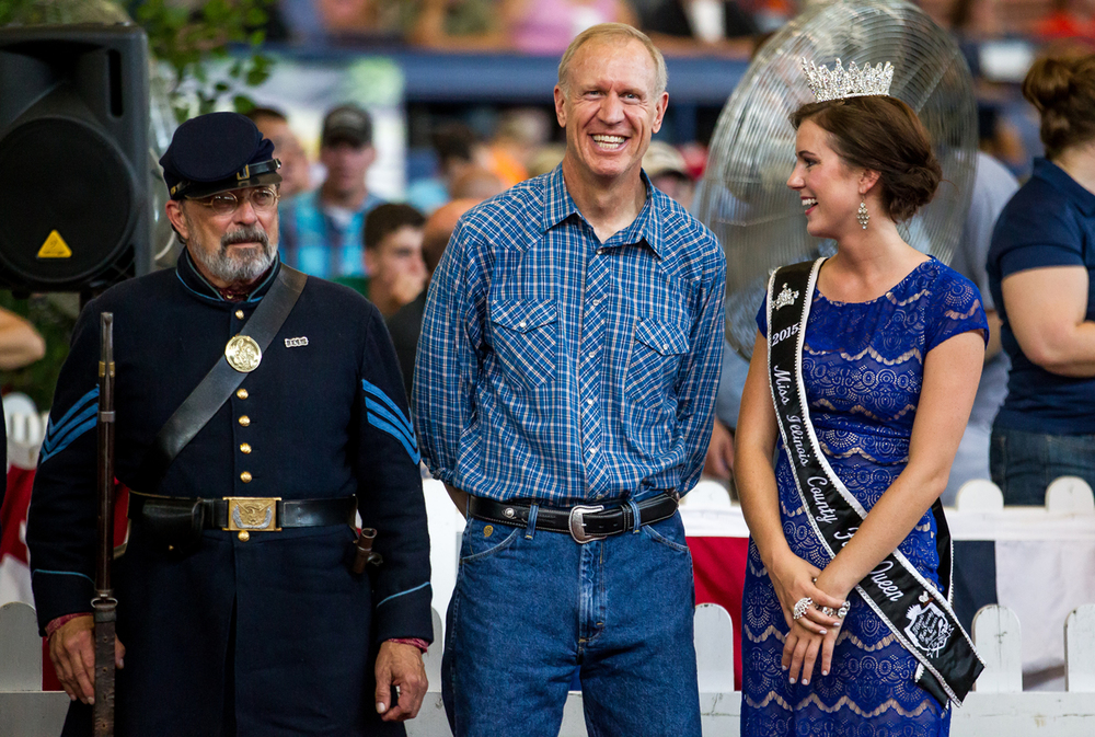 Illinois Gov. Bruce Rauner, center, talks with Sadie Gassmann, Miss Illinois County Fair Queen 2015, during the Parade of Champions in the Coliseum at the Illinois State Fairgrounds, Saturday, Aug. 15, 2015, in Springfield, Ill. Justin L. Fowler/The State Journal-Register