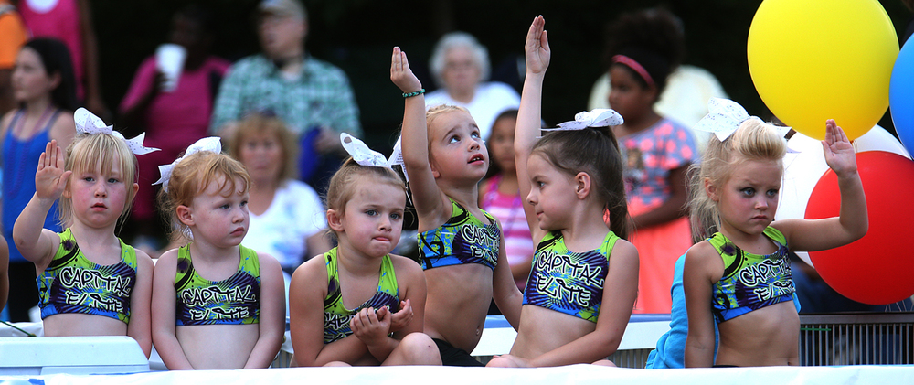 Some of the younger members of the Capital Elite All-Stars cheerleading squad ride on a float during the Illinois State Fair Twilight Parade August 13, 2015. David Spencer/The State Journal-Register