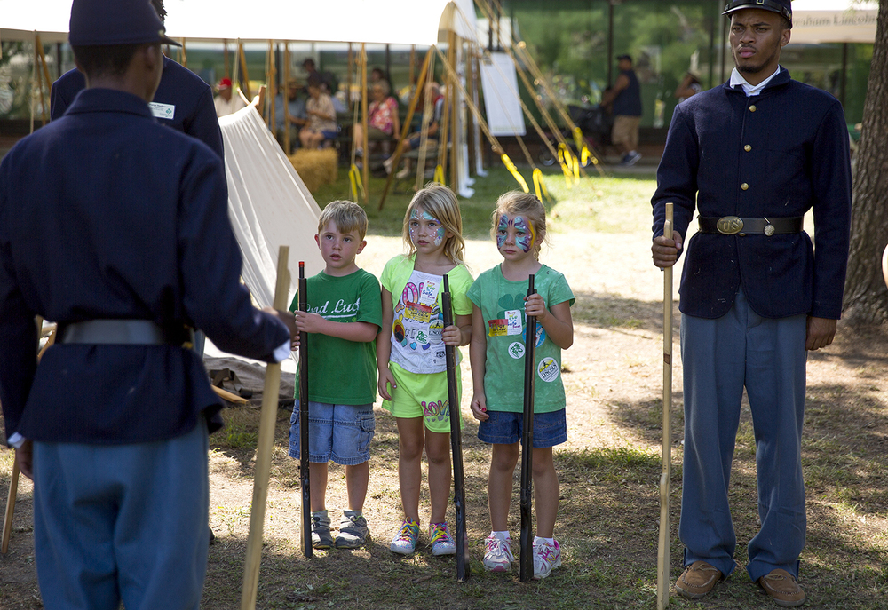 Alli VanVeldhuizen, center, and her friends Mason, left, and June Stehling listen to instructions from Jeremiel Hemingway on how to present arms and march like Civil War soldiers Monday, August 17, 2015 at the Looking for Lincoln area on the Illinois State Fairgrounds. Hemingway and Daryl Jackson, right, along with Wayna Hughes are from the Boys and Girls Club of Springfield and represent the Illinois 29th Regiment of the United States Colored Troops. Rich Saal/The State Journal-Register
