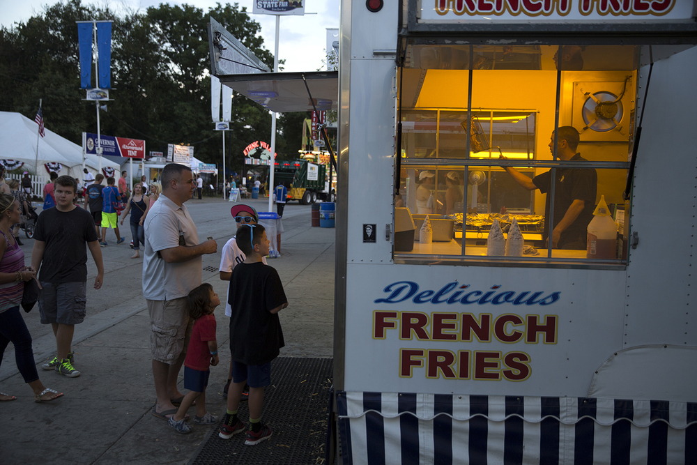 Robert Tuttle shakes the oil from a batch of french fries at a Culler's stand at the Illinois State Fair Monday, August 17, 2015.  Rich Saal/The State Journal-Register
