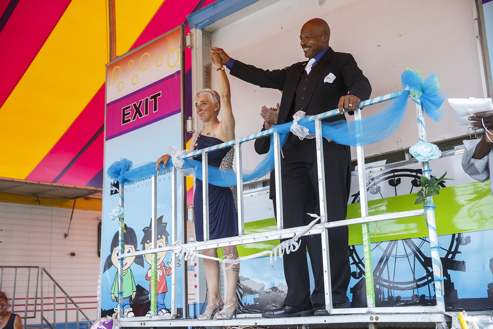 Leonard James and his new bride Tina Karrick of Springfield, Ill., greet the audience gathered for their wedding under a tent near the carnival midway Tuesday, Aug. 18, 2015.  Ted Schurter/The State Journal-Register