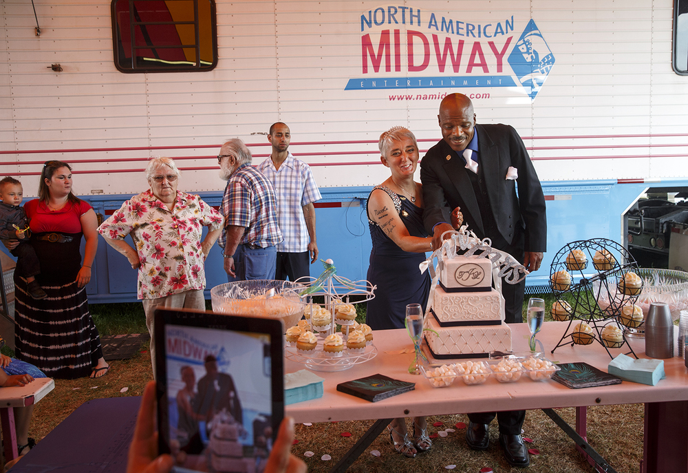 Leonard James and his new bride Tina Karrick of Springfield, Ill., cut their wedding cake during a reception after their wedding under a tent near the carnival midway Tuesday, Aug. 18, 2015. The couple are both employed by North American Midway Entertainment where they met six years ago. Ted Schurter/The State Journal-Register