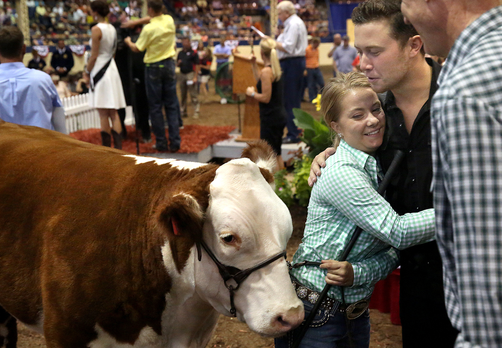 Land of Lincoln Grand Champion Steer winner Taylor Donelson of Clinton gets a hug from American Idol winner Scotty McCreery after McCreery egged on Ill Gov. Bruce Rauner at far right who placed the top bid of $61,000.00 for the steer during the auction. The Governor's Sale of Champions took place in the Coliseum at the Illinois State Fair in Springfield on Tuesday, August 18, 2015. Proceeds from the sale are divided between the individual owners, Illinois FFA and Illinois 4-H programs. David Spencer/The State Journal-Register