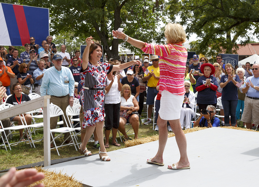 Comptroller Leslie Munger welcomes Lt. Gov. Evelyn Sanguenitti, left, to the stage at the Republican Day rally on the Director's Lawn at the Illinois State Fair Wednesday, Aug. 19, 2015. Rich Saal/The State Journal-Register