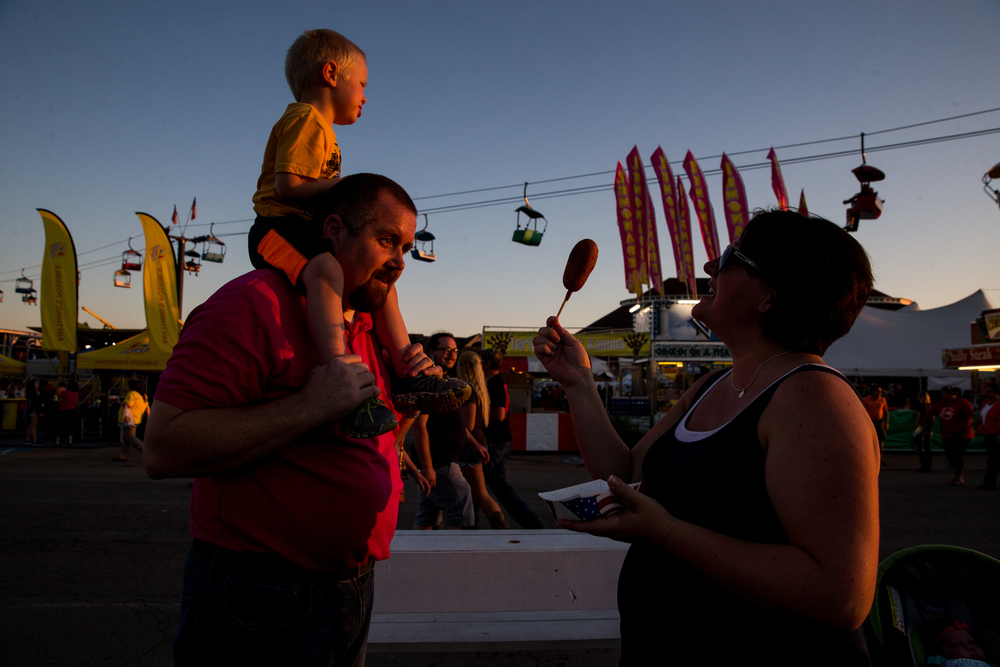 Alexis Call, right, tries to see if her son Carson Call, 2, is ready for his corndog while hitching a ride on the shoulders of his father, Andy Call,  during the Illinois State Fair, Thursday, Aug. 20, 2015, in Springfield, Ill. Justin L. Fowler/The State Journal-Register