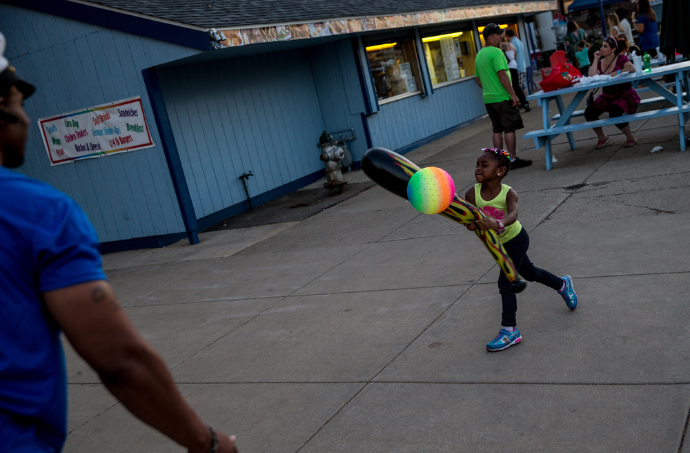 Kira Perry, 4, plays with an inflatable ball and bat with her father Douglas Perry, left, outside of the Coliseum at the Illinois State Fairgrounds, Thursday, Aug. 20, 2015, in Springfield, Ill. Justin L. Fowler/The State Journal-Register