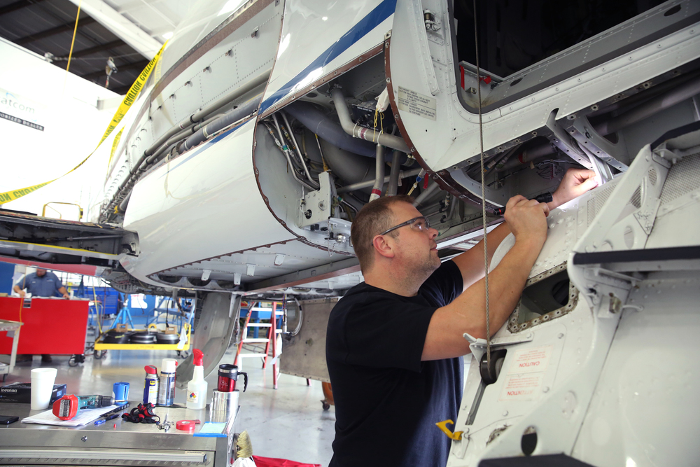 StandardAero employee Phillip Kubat performs an airframe inspection on the rear of a French-made Falcon 900 corporate jet being refurbished at the airport. David Spencer/The State Journal-Register