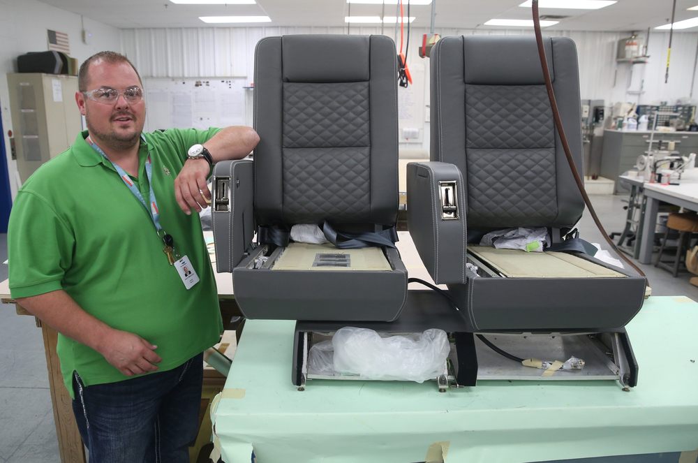StandardAero Vice President and General Manager Kevin Malutinok shows off a pair of newly upholstered leather seats. David Spencer/The State Journal-Register