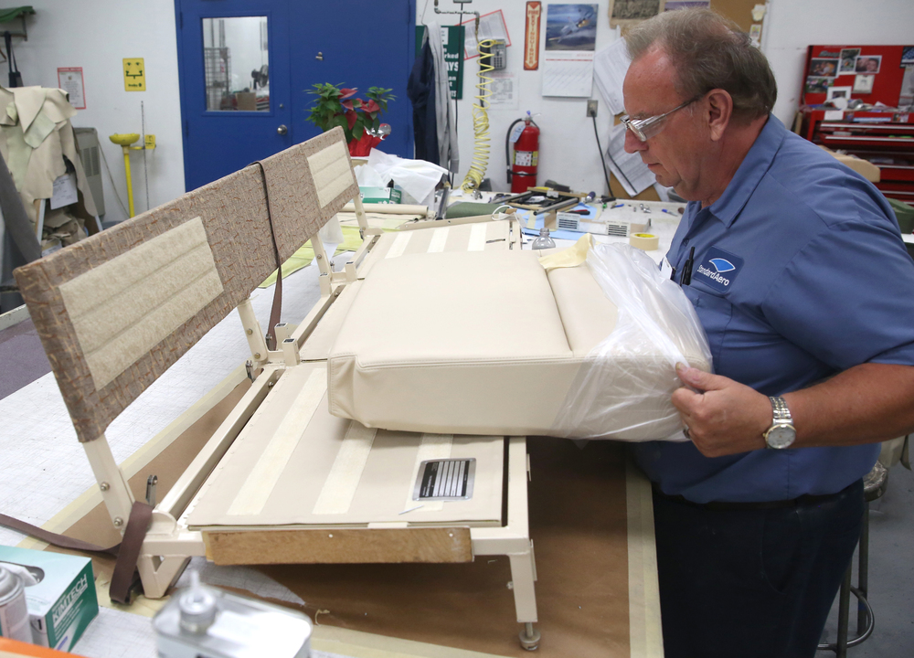 StandardAero upholsterer Terry Cole shows off a brand-new leather seat cushion recently fabricated for this divan which will be put back into the cabin area of a Falcon 900 corporate jet. David Spencer/The State Journal-Register