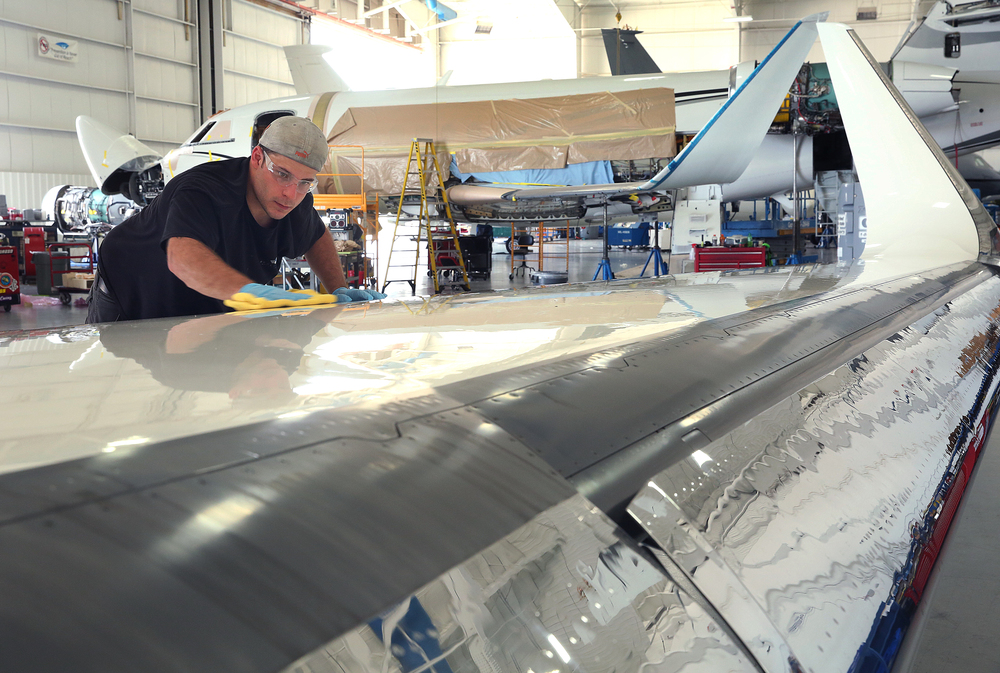 StandardAero detailer Matt Miller buffs out the top of a newly-painted wing of a Falcon 900 jet at the airport. David Spencer/The State Journal-Register