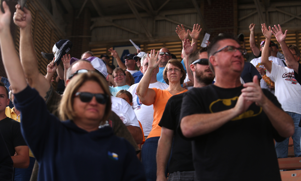 Race fans stand in the grandstand while raising their hands to salute the drivers at the very start of the race.  David Spencer/The State Journal-Register