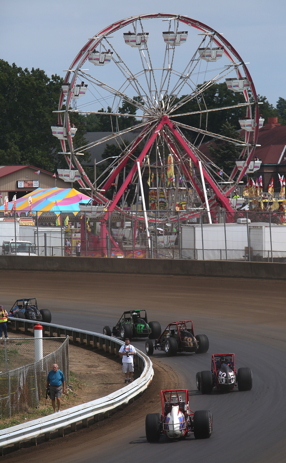 With the Midway ferris wheel seen in the distance, cars go enter the first turn of the race track Saturday afternoon. David Spencer/The State Journal-Register
