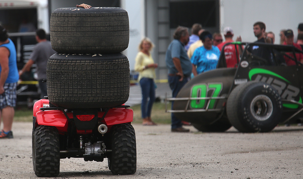 An ATV driver keeps one hand on a set of tires being transported through pit row at the conclusion of the race Saturday afternoon. David Spencer/The State Journal-Register
