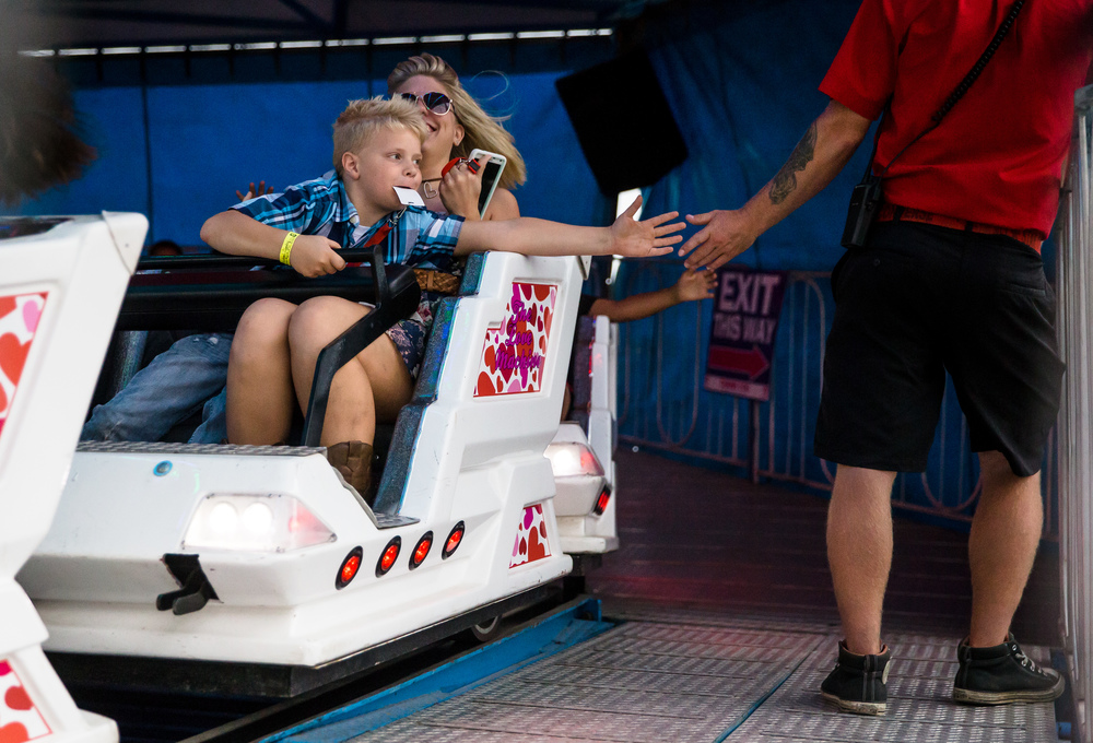 Michael Cumby, 7, reaches across his mother, Nicole Cumby, as he tries to get a high five while riding the roller coaster in the North American Midway at the Illinois State Fair, Saturday, Aug. 22, 2015, in Springfield, Ill. Justin L. Fowler/The State Journal-Register