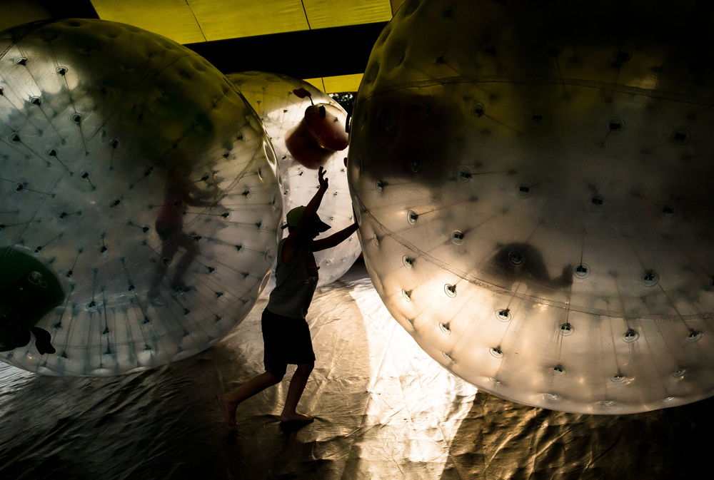 Youngsters throw their weight behind the inflatable balls as they get tossed around in the inner chamber while bumping into each other at the attraction in Happy Hollow at the Illinois State Fair, Saturday, Aug. 22, 2015, in Springfield, Ill. Justin L. Fowler/The State Journal-Register