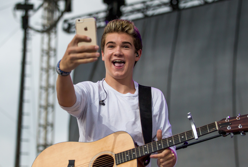 Devin Hayes sends a Snapchat from the stage of his fans while performing on the Grandstand as an opening act for Austin Mahone at the Illinois State Fair, Saturday, Aug. 22, 2015, in Springfield, Ill. Justin L. Fowler/The State Journal-Register