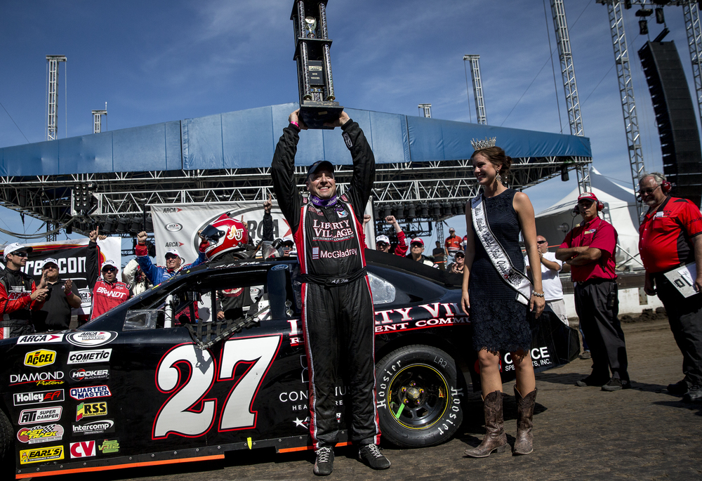 A.J. Fike raises the trophy next to 2015 Miss Illinois State Fair Queen Sadie Gassmann after taking his Liberty Village-Office Specialists Ford to victory lane in the SuperChevyStores.com 100/Allen Crowe Memorial at the Illinois State Fair, Sunday, Aug. 23, 2015, in Springfield, Ill. Justin L. Fowler/The State Journal-Register