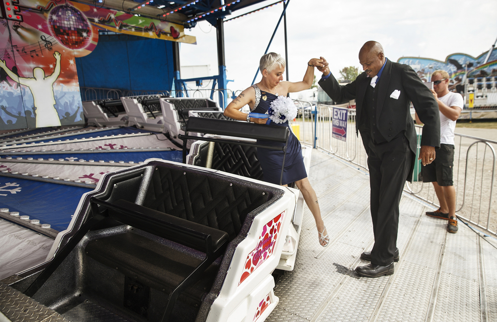 Leonard James helps his new bride Tina Karrick of Springfield, Ill., off the Love Machine ride at the Illinois State Fair Tuesday, Aug. 18, 2015. The couple, both employed by North American Midway Entertainment where they met six years ago, were wed under a tent near the carnival midway and took a spin on the ride after their ceremony. Ted Schurter/The State Journal-Register