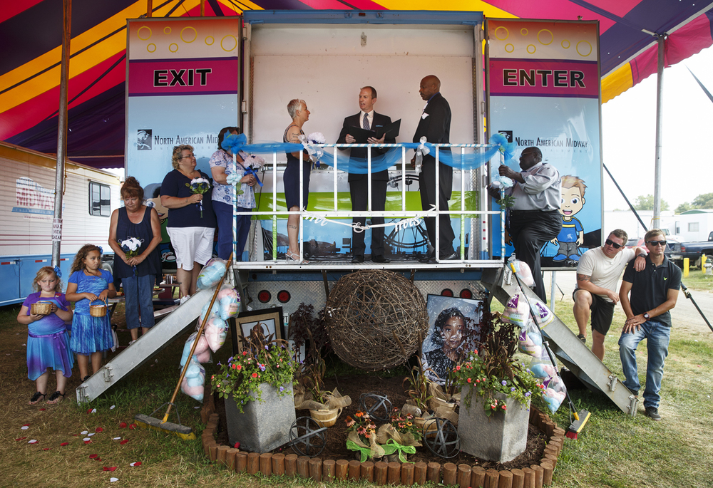 Reverend Scott Raper presides over the wedding between carnival empolyees Tina Karrick and Leonard James under a tent near the carnival midway at the Illinois State Fair Tuesday, Aug. 18, 2015. Ted Schurter/The State Journal-Register