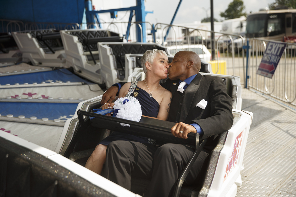 Leonard James kisses his new bride Tina Karick of Springfield, Ill., as they ride the Love Machine at the Illinois State Fair Tuesday, Aug. 18, 2015. The couple, both employed by North American Midway Entertainment where they met six years ago, was wed under a tent near the carnival midway and took a spin on the ride after their ceremony. Ted Schurter/The State Journal-Register