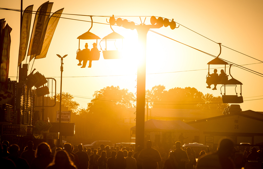 The sun begins to set over the Illinois State Fairgrounds as fairgoers make their way down Illinois Central during the Illinois State Fair, Thursday, Aug. 20, 2015, in Springfield, Ill. Justin L. Fowler/The State Journal-Register