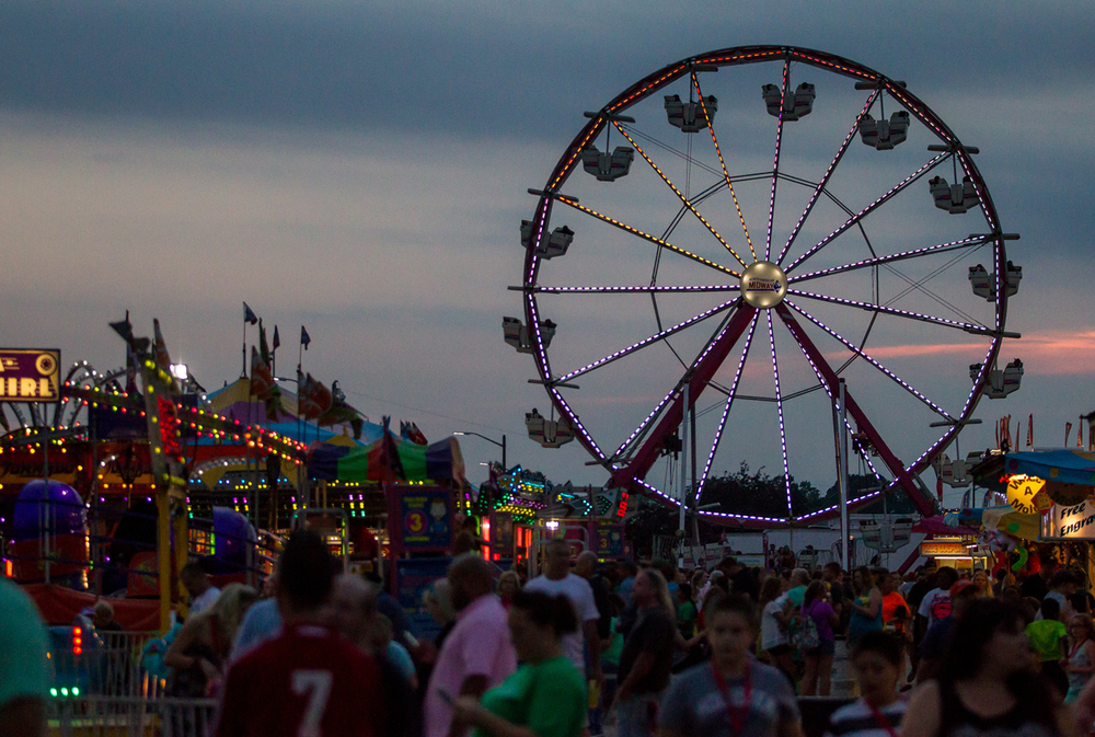 The ferris wheel in the North American Midway begins to light up as the sun sets at the Illinois State Fair, Saturday, Aug. 22, 2015, in Springfield, Ill. Justin L. Fowler/The State Journal-Register