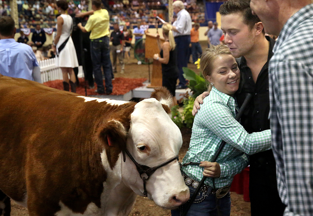 Land of Lincoln Grand Champion Steer winner Taylor Donelson of Clinton gets a hug from American Idol winner Scotty McCreery after McCreery egged on Ill Gov. Bruce Rauner at far right who placed the top bid of $61,000.00 for the steer during the auction. McCreery was scheduled to perform on the Grandstand Stage Tuesday evening after the auction. The Governor's Sale of Champions took place in the Coliseum at the Illinois State Fair in Springfield on Tuesday, August 18, 2015. Proceeds from the sale are divided between the individual owners, Illinois FFA and Illinois 4-H programs. David Spencer/The State Journal-Register