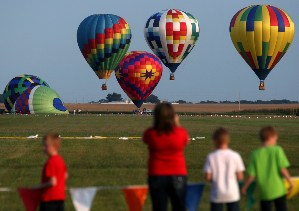Visitors to the preview night watch as hot air balloons rise in the distance at the airport Thurday night. David Spencer/The State Journal-Register