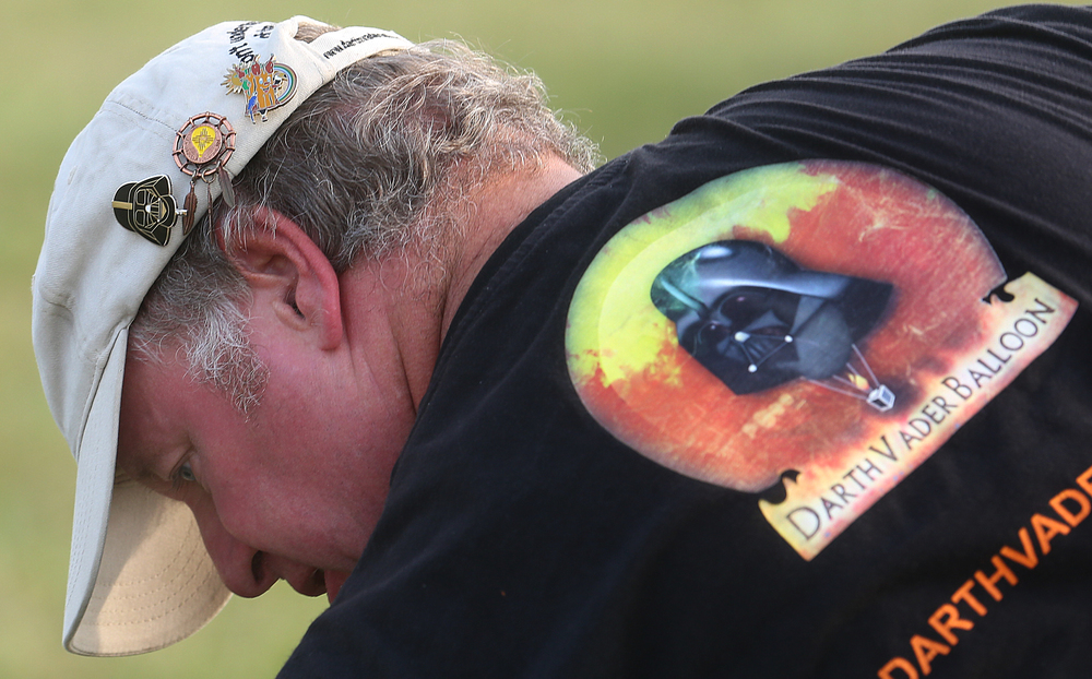 Hot air balloon pins adorn a ballcap worn by Darth Vader balloon owner and pilot Michel Lambert of Belgium seen here prepping the balloon for launch Thursday evening. David Spencer/The State Journal-Register