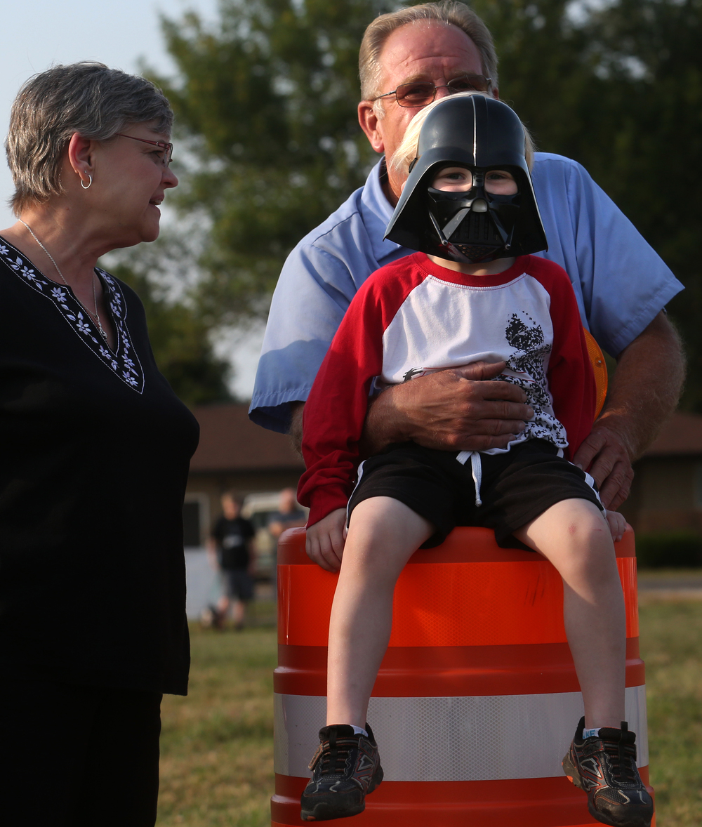 Tommy Soloman, 5 of Lincoln, wears his Darth Vader mask while watching the Darth Vader balloon inflate along with grandparents Suzi, left, and Roger Alsup. David Spencer/The State Journal-Register