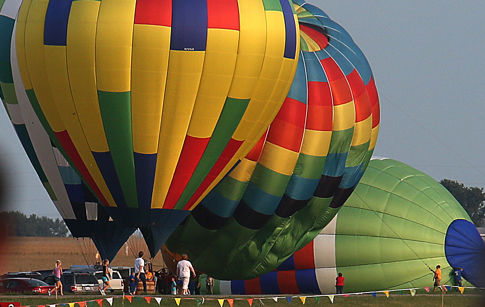 A small number of colorful hot air balloons are inflated Thursday evening at the airport before being launched. David Spencer/The State Journal-Register