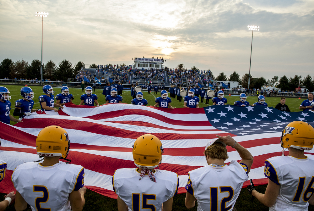 The Auburn Trojans and the Williamsville Bullets take to the field with an American Flag for the National Anthem prior to kickoff at Michael J. Potts Memorial Field, Friday, Aug. 28, 2015, in Auburn, Ill. Justin L. Fowler/The State Journal-Register