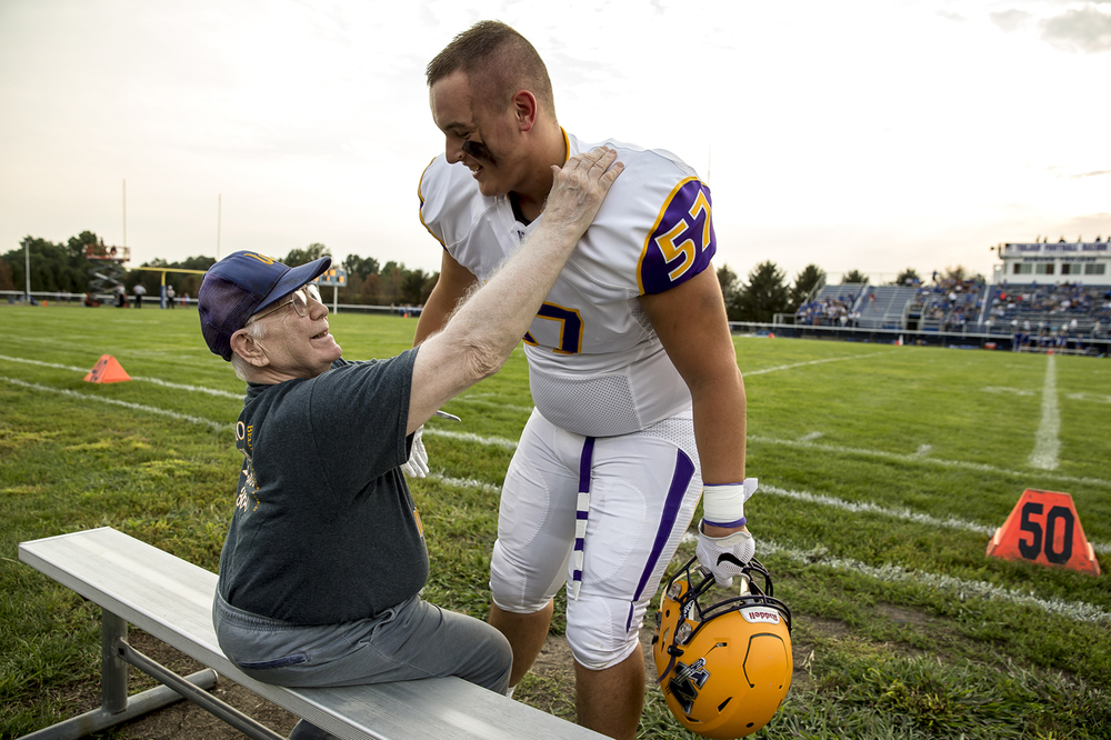 Williamsville's Austin Spencer (57) gets a hug from long time Williamsville trainer Jim Byron, left, prior to kickoff as the Bullets take on Auburn at Michael J. Potts Memorial Field, Friday, Aug. 28, 2015, in Auburn, Ill. Justin L. Fowler/The State Journal-Register
