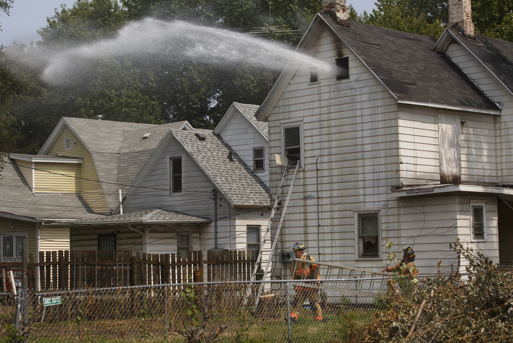A pair of firefighters from the Springfield Fire Department move a ladder to the back of a vacant house as water is sprayed through the attic window in the 1500 block of South Eighth St. Thursday, Aug. 27, 2015. Ted Schurter/The State Journal-Register