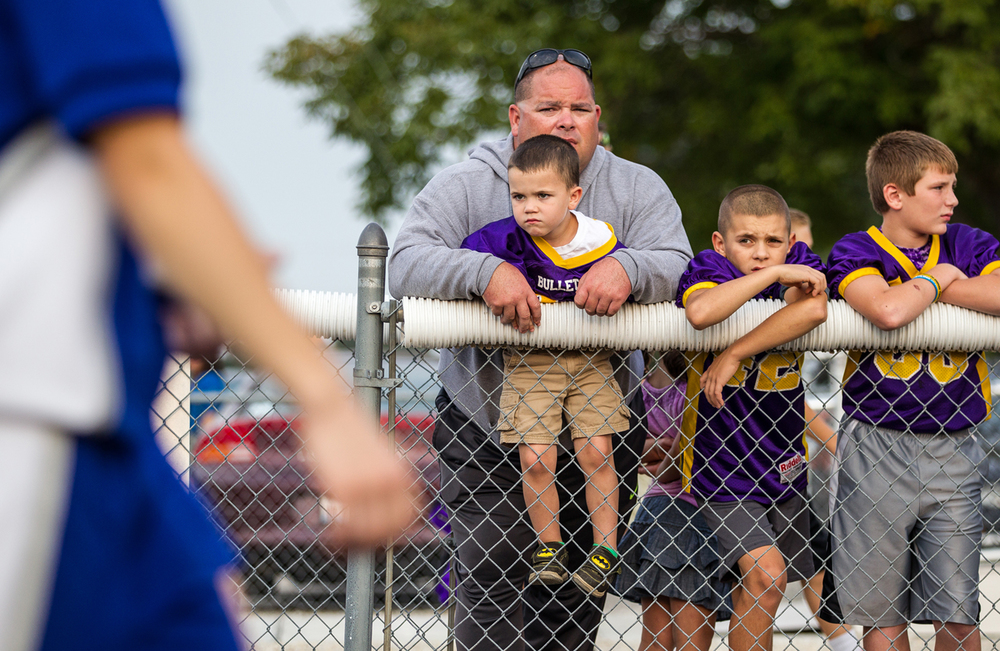 Andrew Mumaw, 5, gets a little help over the fence from his father, Steve Mumaw, as Williamsville takes on Auburn at Michael J. Potts Memorial Field, Friday, Aug. 28, 2015, in Auburn, Ill. Justin L. Fowler/The State Journal-Register
