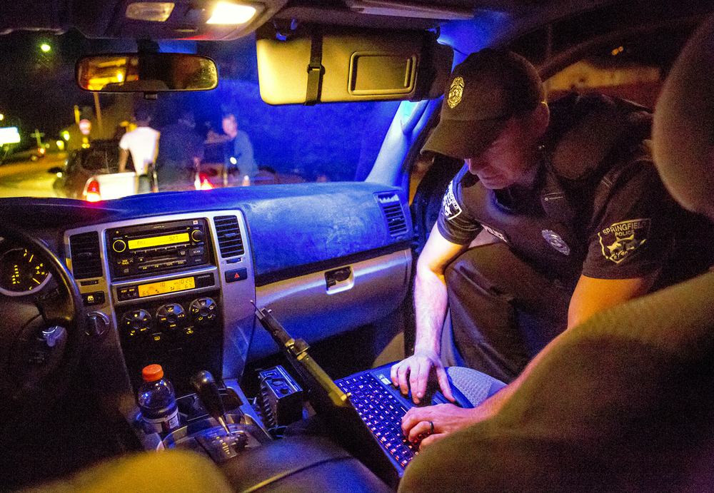 Officer Anthony McClenathan, of the Springfield Police Department's Street Crimes Unit, runs through information on a person described as a suspect and a victim in multiple shots fired incidents that was pulled over after McClenathan spotted the suspect's vehicle, Thursday, Aug. 27, 2015, in Springfield, Ill. Justin L. Fowler/The State Journal-Register