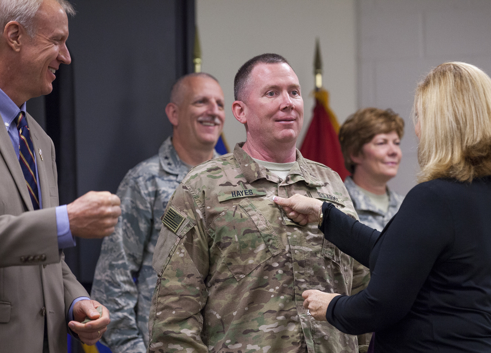 Brig. Gen. Richard Hayes Jr. was promoted to major general and received his second star from Gov. Bruce Rauner in a ceremony at Camp Lincoln, headquarters of the Illinois National Guard, Monday, Aug. 24, 2015. Danette Hayes uses her fist to secure the Velco, two-star patch on her husband's uniform. Hayes was named by Rauner Illinois adjutant general in June and his promotion was confirmed by the U.S. Senate earlier this month. Hayes oversees operations of the Illinois National Guard, which includes 13,000 military and 230 civilian employees. Rich Saal/The State Journal-Register