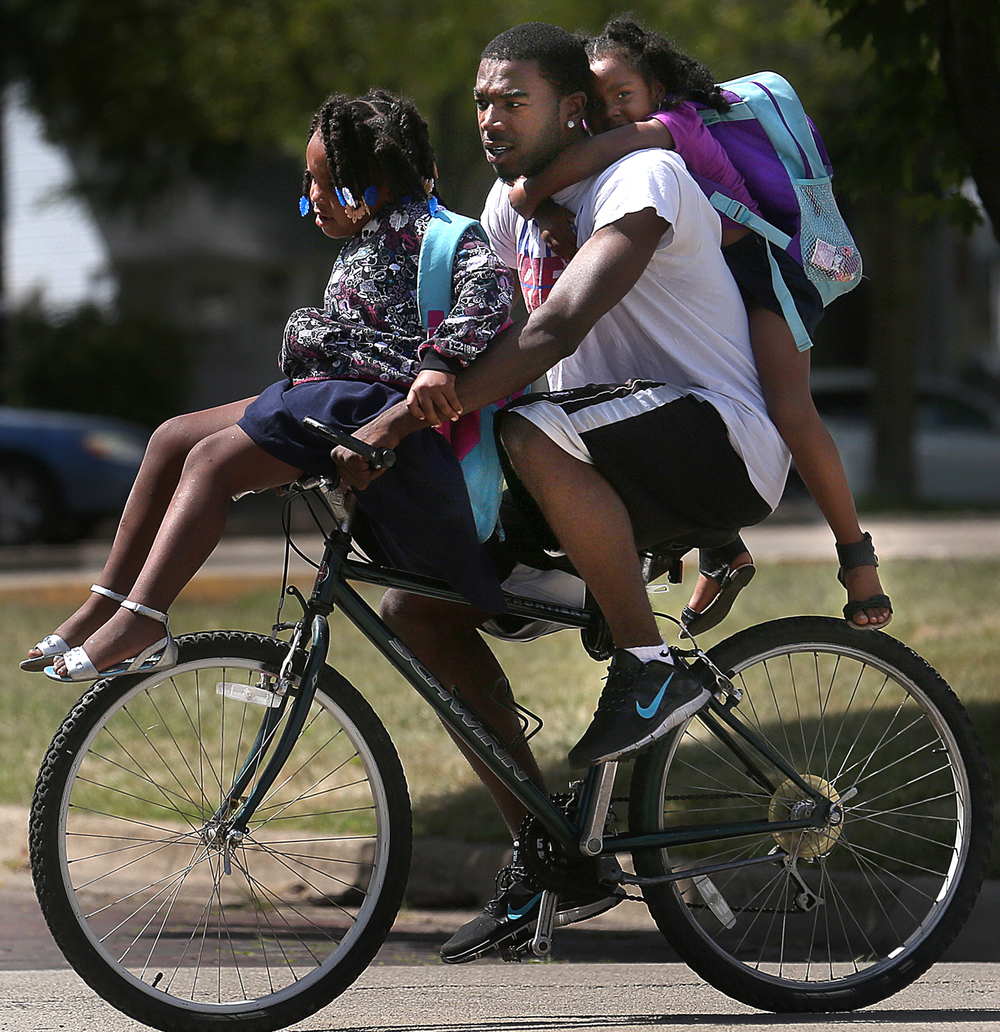 Chris Davis makes his way down the sidewalk on South Fifth Street to his home with his daughter Naveyah Davis, 5 in front and his niece, Harmoni Turner, 5 in back. Davis gave the girls a ride home from school. David Spencer/The State Journal-Register