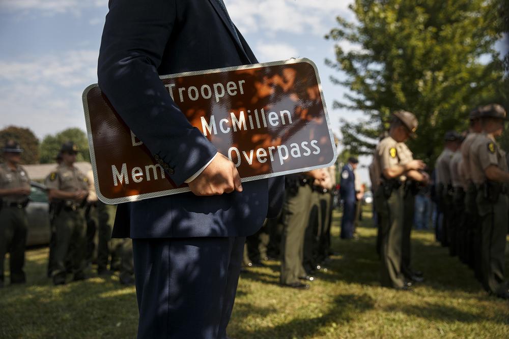 "Jared Thornley holds a ""Trooper Brian McMillen Memorial Overpass"" sign as Illinois State Police troopers wait in formation during a ceremony to mark the dedication of the Dye Road overpass over Interstate 72 as the ""Trooper Brian McMillen Memorial Overpass"" Friday, Sept. 4, 2015. Ted Schurter/The State Journal-Register"