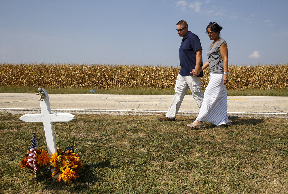 "Andrew and Grace Thompson visit the roadside memorial for Illinois State Police Trooper Brian McMillen, who was killed responding to a call Oct. 28, 2007, after a ceremony to mark the dedication of the Dye Road overpass over Interstate 72 as the ""Trooper Brian McMillen Memorial Overpass"" Friday, Sept. 4, 2015. Andrew worked with McMillen at the Illinois Air National Guard. Ted Schurter/The State Journal-Register"