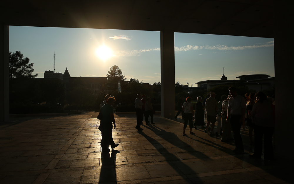 Tour visitors are silhoutted as they head to the next stop while exiting the massive ground-floor patio which encircles the base of the Horace Mann building.  David Spencer/The State Journal-Register