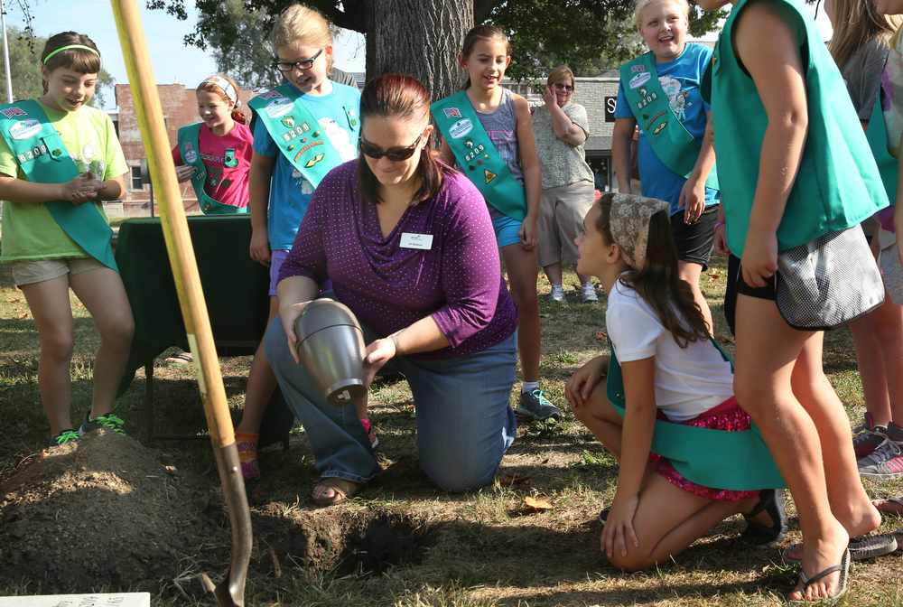 Jill Waltman, a Girl Scout troop leader for Troop #6209, places a sealed urn containing items gathered from troop members into the ground in Community Park on the village square early Saturday morning. Scouts included Waltman's daughter Jasmine Brown, 9 at lower right. The time capsule is scheduled to be opened on Sept. 5, 2065. David Spencer/The State Journal-Register